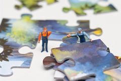 Two workers put puzzles. The concept of teamwork Stock Photos
