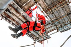 Work at height by rope access. Two workers with red boiler suit work at height one of them low down by rope access stock photos