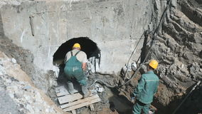 Two workers repairing a manifold outdoors. Two men repairing a manifold with a special equipment. They are wearing a dirty uniform and helmets. Soil around them stock footage