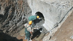 Two workers repairing a manifold outdoors. Two men repairing a manifold with a special equipment. They are wearing a dirty uniform and helmets. Soil around them stock video