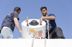 Two workers on the roof with a solar water heater- Mitzpe Ramon, Israel. Middle East - Mitzpe Ramon, Israel. February 29,The installation of new solar water royalty free stock photography