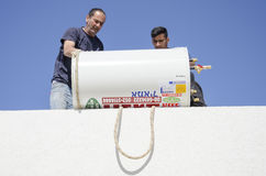 Two workers on the roof with a solar water heater- Mitzpe Ramon, Israel. Middle East- Mitzpe Ramon, Israel. February 29,The installation of new solar water royalty free stock photo