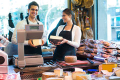 Two workers selling cheese and sausages Stock Images