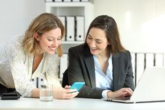 Two workers sharing smartphone content. Two happy workers sharing smartphone content at office Stock Photos