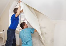 Two workers smoothing wallpaper Stock Image