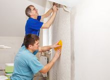 Two workers smoothing wallpaper Stock Photos