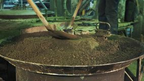 Two workers spread cement with shovels over vibrating machine metal cauldron. Two unrecognisable workers spread cement with shovels over vibrating machine metal stock video footage