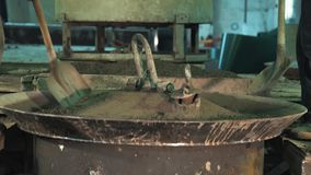 Two workers spread concrete with shovels over vibrating machine metal bowl. Two unrecognisable workers spread concrete with shovels over vibrating machine metal stock footage