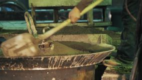 Two workers spread concrete with shovels over vibrating machine metal cauldron. Two unrecognisable workers spread concrete with shovels over vibrating machine stock video footage