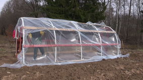 Two workers in spring farm make new plastic greenhouse. And wind stock video footage