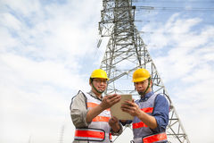 Two workers standing before electrical power tower Royalty Free Stock Images