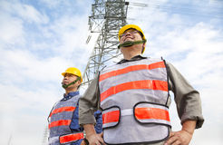 Two workers standing before electrical power tower Royalty Free Stock Photos