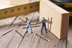 Two workers sticks nail. The concept of teamwork Royalty Free Stock Photo