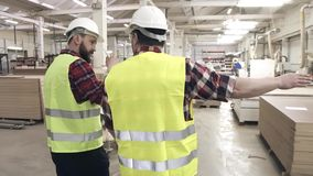 Two workers talking in green waistcoats and helmets at a furniture factory among machines. Two men are walking around the furniture factory talking stock video
