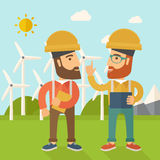 Two workers talking infront of windmills. Stock Photography