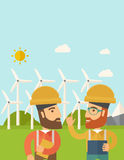 Two workers talking infront of windmills. Royalty Free Stock Photography