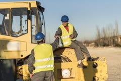 Two workers talking in work break on steamroller bulldozer vehic Royalty Free Stock Photos