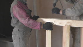 Two workers tighten screw a Board drill. 