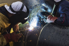 Two workers together welding big tube Stock Photos