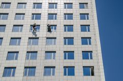 Two workers wash the windows on a high-rise building. Two workers wash windows on a high-rise building royalty free stock images
