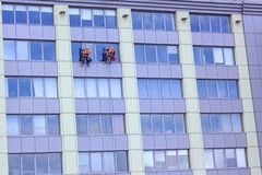 Two Workers Washing A Skyscraper Windows. Two workers of steeplejack washing a skyscraper windows Royalty Free Stock Photos