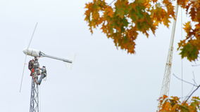 Two workers wearing helmets renovating a home wind turbine. stock footage