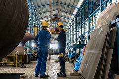 Two workers wearing yellow hard hat and blue uniform. In the interior of an industrial hall stock photo