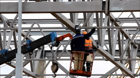 Two workers weld metalwork at height using an industrial elevator. stock video