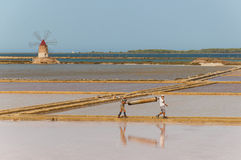 Two workers at the west coast salt pans in Marsala Royalty Free Stock Image