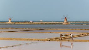 Two workers at the west coast salt pans in Marsala Royalty Free Stock Photography