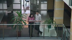 Two workers woman man discussing business project standing in hall. Female brunette in blue red plaid shirt tie bow, black skirt stand on second floor next to stock video