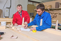 Two workers at a wooden workbench royalty free stock image