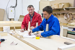 Two workers at a wooden workbench Stock Images