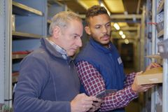Two workers workers in warehouse. Warehouse royalty free stock images