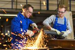 Two workers working with angle grinder Royalty Free Stock Photography