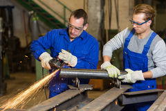 Two workers working with angle grinder Stock Image