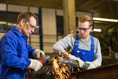 Two workers working with angle grinder. In steel construction Stock Images