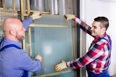 Two workers working with glass Royalty Free Stock Photos