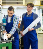 Two  workers working on a machine Royalty Free Stock Photos