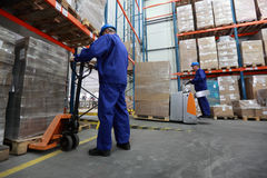 Two workers working in storehouse. Two workers in blue uniforms and safety helmets working in storehouse Stock Image