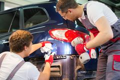 Two workers in a workshop. Two workers with colour samples choosing correct shade in a car body workshop Stock Photo