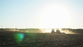 Two working forces in the field. Iridescent reflections fall into the chamber, the tractor makes a turn stock footage