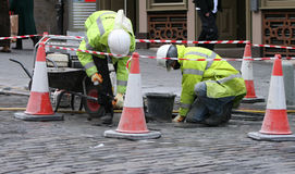 Two workman repairing pavement Royalty Free Stock Photos