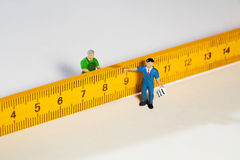 Two Workmen Figurines With A Ruler Royalty Free Stock Photo