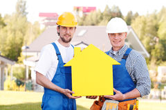 Two workmen and house symbol Stock Photography