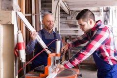 Two workmen in PVC shop Stock Image