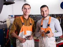 Two workmen toiling in workshop Stock Image