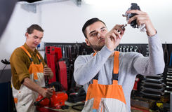 Two workmen toiling in workshop Stock Photography