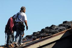 Two workmen walking on roof of building Royalty Free Stock Photo