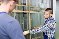 Two  workmen working with glass Stock Image
